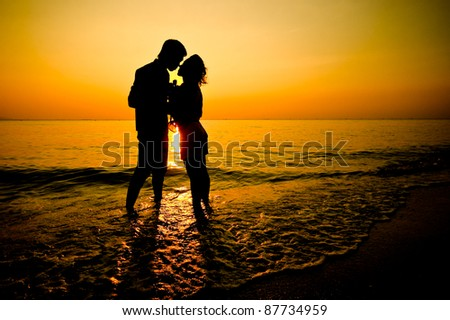 Silhouette of a young romantic couple  on sunset - stock photo