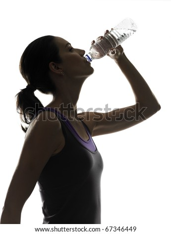 silhouette of a young sportive woman drinking water - stock photo