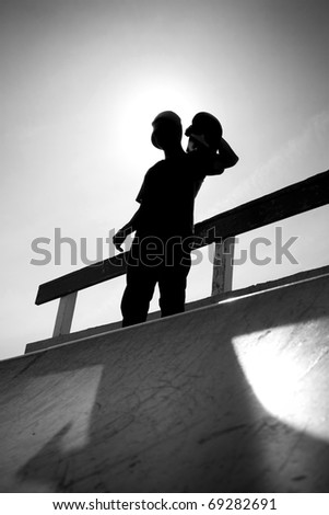 Silhouette of a young teenage skateboarder at the top of the half pipe ramp at the skate park. - stock photo