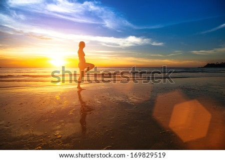 Silhouette of a young woman doing exercises at sunset on the seashore. - stock photo
