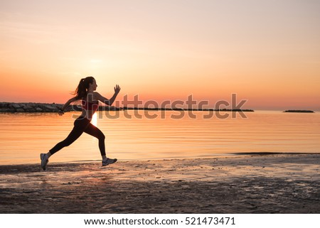 Silhouette of a young woman have her running workout at the beach during the sunset
