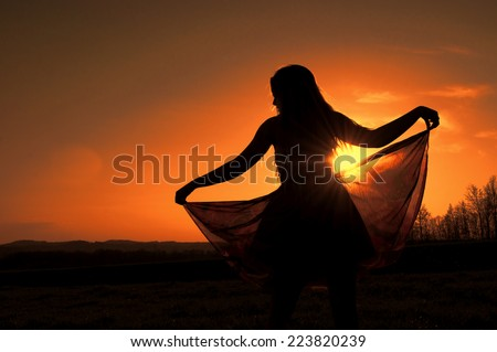 Silhouette of a young woman in a floaty dress - stock photo