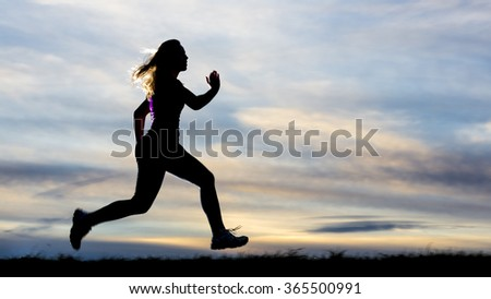 silhouette of a young woman jogging in sundown - stock photo