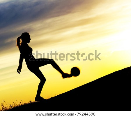 Silhouette of a young woman playing football  against yellow sky with clouds