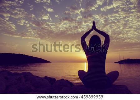 Silhouette of a young woman practicing yoga on a rocky shore in Syvota bay, Greece. Cloudy sky, Ionian sea and a beautiful sunset in the background.