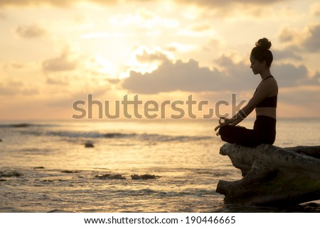Silhouette of a young woman practicing yoga on the beach at sunrise - stock photo