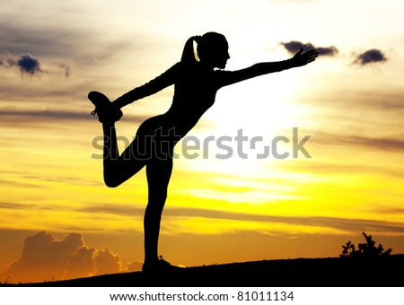 Silhouette of a young woman practicing yoga on the hill against yellow sky with clouds at sunset - stock photo