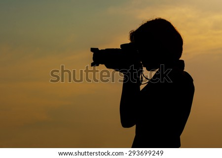 Silhouette of a young woman shooting with a camera, against late evening sunset clouds
