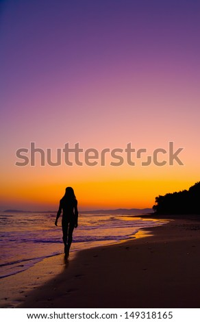 Silhouette of a young woman walking on a beach at sunset in Tuscany, Italy./Silhouette of girl walking on a beach at sunset - stock photo