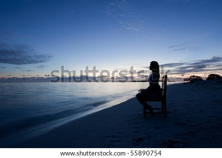 Silhouette of a young woman watching the ocean during nightfall - stock photo