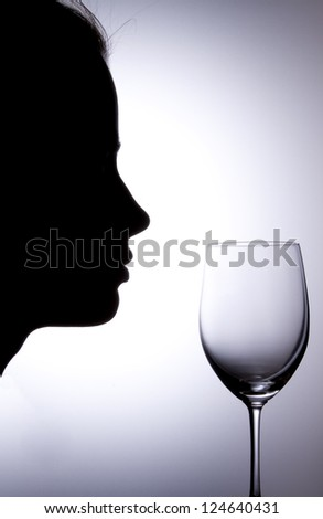 Silhouette of a young woman with vine glass - stock photo
