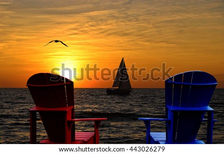 silhouette of Adirondack chairs facing Lake Michigan sunset with sailboat