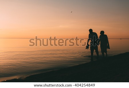 Silhouette of adult couple walks on the seashore against a sunset. Evening photo.