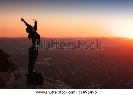 Silhouette of African American Business Woman on top of Hill during Sunset - stock photo