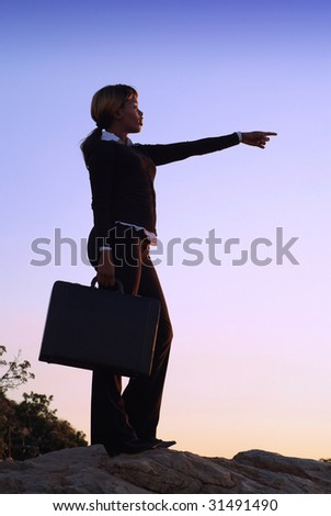 Silhouette of African American Business Woman Standing with Outstretched Arm on Hill Top - stock photo