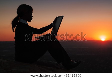 Silhouette of African American Business Woman Working with Laptop during Sunset on top of a Hill - stock photo
