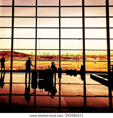 Silhouette of airline passengers in an airport lounge looking through a wide observation window at a surreal sunset in the horizon - stock photo
