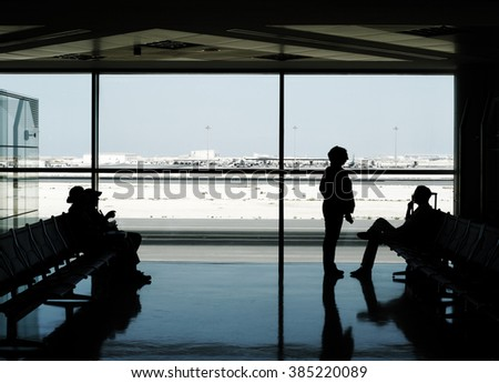 Silhouette of airline passengers waiting at an airport lounge with a wide observation window showing the airport runway. - stock photo