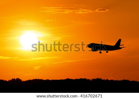 silhouette of airplane at sunset