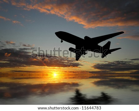 Silhouette of airplane over sunset - stock photo