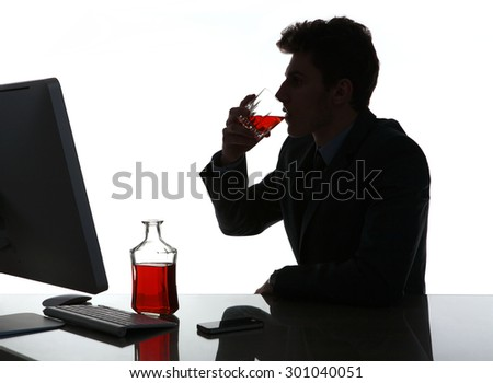 Silhouette of alcoholic drunk young man drinking rum / photo of businessman addicted to alcohol at the workplace, depression and crisis concept - stock photo