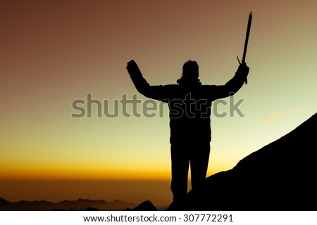 Silhouette of alpinist celebrating. Person holding ice axe at sunrise.
