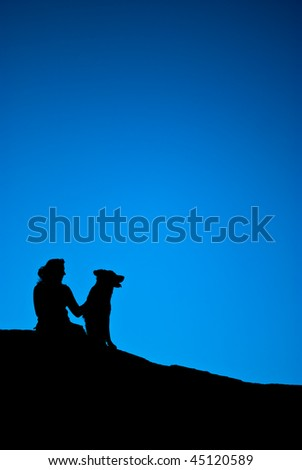 Silhouette of an Adult female and pet dog sitting on a hill with a cobalt blue background.