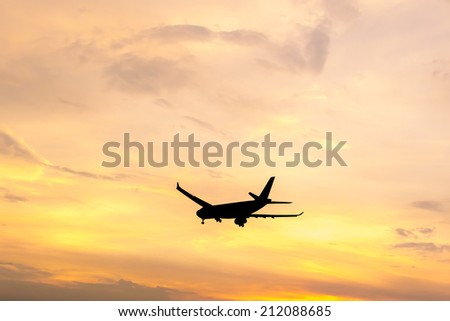 Silhouette of an aircraft flying in dramatic sunset sky - stock photo