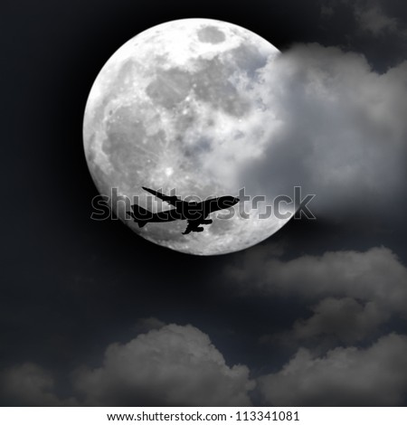 Silhouette of an airplane flying across a full moon at twilight. - stock photo