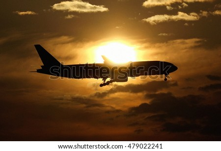 Silhouette of an airplane flying with rising sun in the background