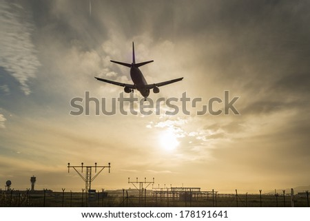 Silhouette of an airplane landing at dusk.