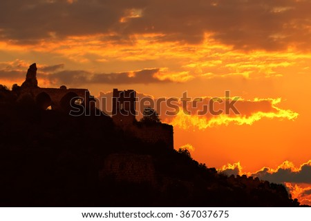 """Silhouette of an ancient Crusaders Montfort castle ( """"Mountain Fortress"""" ) at Mediterranean sunset.The Upper Galilee mountains. National park and popular tourist and historic site. Israel.  - stock photo"""