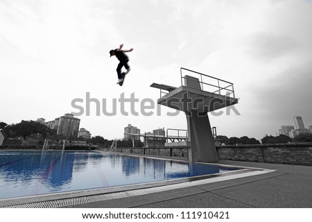 Silhouette of an energetic skateboarder jumping off a diving platform against a dramatic cloudy sky into a blue swimming pool. - stock photo