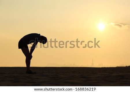Silhouette of an exhausted sportsman at sunset with the horizon in the background - stock photo