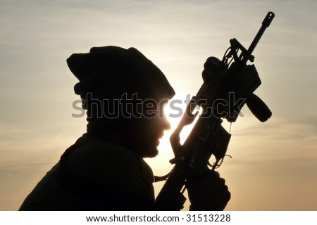 Silhouette of an IDF soldier testing his M16 - stock photo