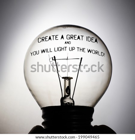 Silhouette of an incandescent light bulb with the message: Create a great idea and you will light up the world! - stock photo