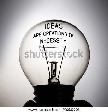Silhouette of an incandescent light bulb with the message: Ideas are Creations of Necessity!  - stock photo