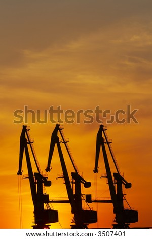 Silhouette of an industrial dock crane unloading at sunset