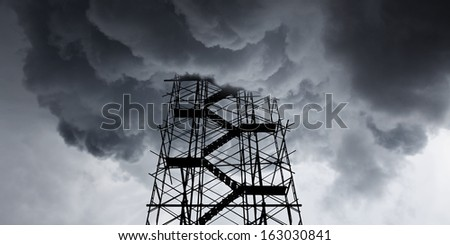 Silhouette of an industrial scaffold frame climbing up into a stormy thunder cloud.  - stock photo