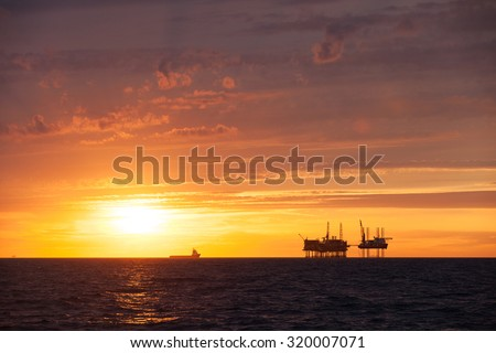 Silhouette of an offshore oil platform and supply vessel at sunset - stock photo