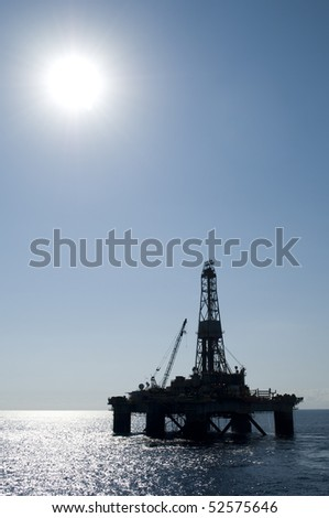 Silhouette of an oil drilling rig in offshore area, during very calm seas and blue sky - stock photo