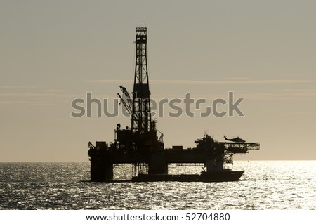 silhouette of an oil drilling rig, in offshore area, with a supply vessel along side and helicopter landed. - stock photo