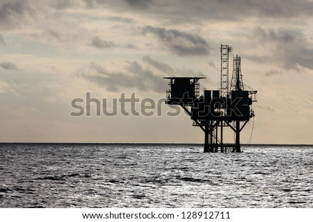 Silhouette of an oil production platform deep in the Gulf of Mexico - stock photo
