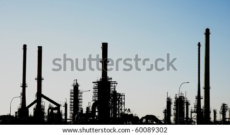 Silhouette of an oil refinery with pipes and chimneys - stock photo