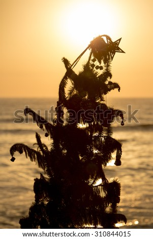 Silhouette of an old christmas tree standing by the beach with ocean and a beautiful sunset in Miraflores. Lima - Peru - stock photo