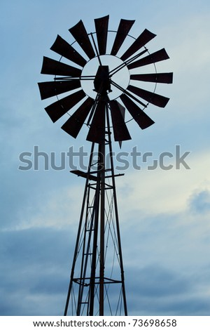 Silhouette of an old fashioned windmill against cloudy sky