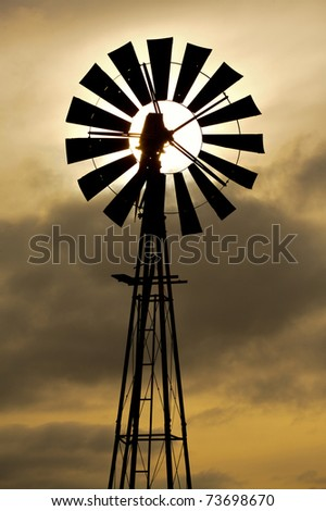 Silhouette of an old fashioned windmill against cloudy sunset sky - stock photo