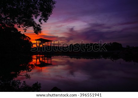 silhouette of an old jetty at sunset - stock photo