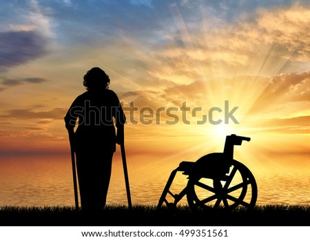 Silhouette of an old woman on crutches on a background of sea sunset and wheelchair. Concept of disability and old age