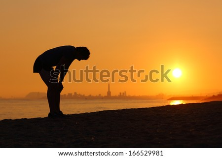 Silhouette of an tired sportsman at sunset with a city in the background - stock photo